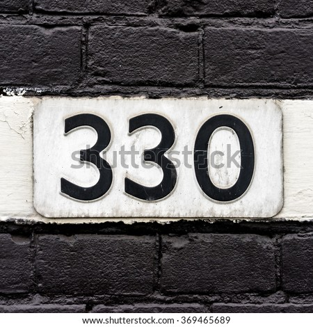 House number three hundred and thirty three embossed in a metal plate. - stock photo