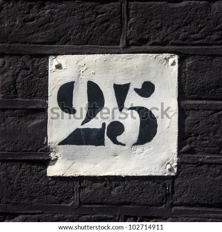 house number twenty five. Black template lettering on a white painted plate.