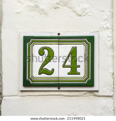House number twenty four, green lettering on two separate ceramic tiles. - stock photo