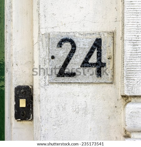 House number twenty four, next to a door bell. - stock photo