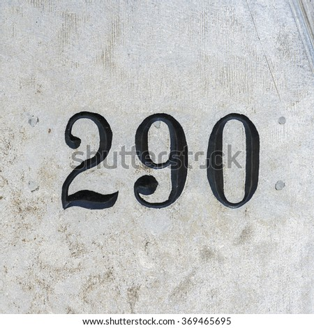 House number two hundred and ninety engraved in a stone wall. - stock photo