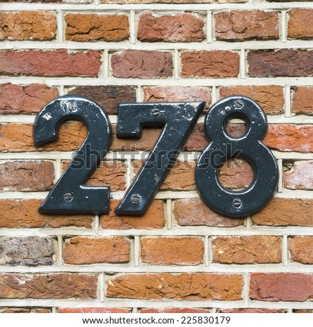 house number two hundred and seventy eight. Separate lettering on a red brick wall. - stock photo