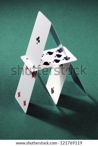 house of cards built on the green table gaming - stock photo