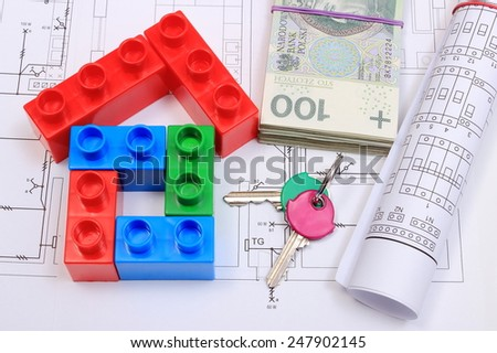 House of colorful building blocks, home keys, banknotes and electrical diagrams lying on construction drawing of house, concept of building house, drawings for projects - stock photo