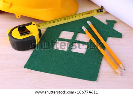 House of felt with helmet on wooden background - stock photo