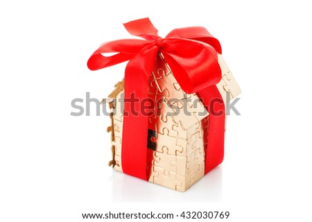 house of gold color puzzles with red bow. Real estate concept  - stock photo