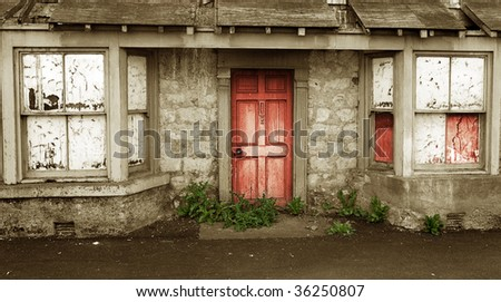 House of Horrors Concept with decayed creepy Entrance with weeds around Red stained Door - stock photo