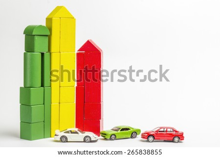 House of wooden blocks of different colors, three wooden figures of trees, euro money, three models of cars, keychains