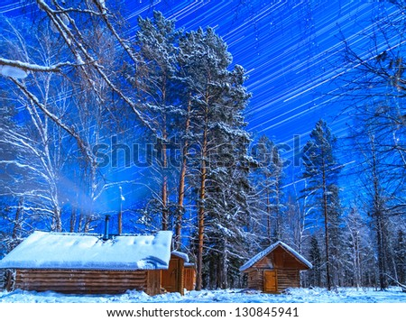House on a moonlit night. Star tracks - stock photo