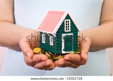 House on a pile of golden coins in woman hands - stock photo
