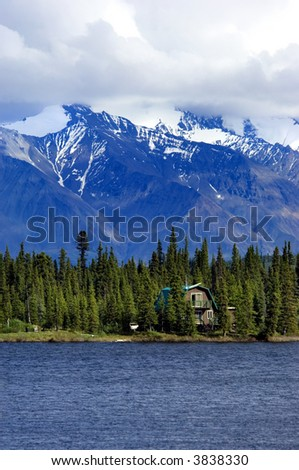 House on Alaskan lake with mountain range on background