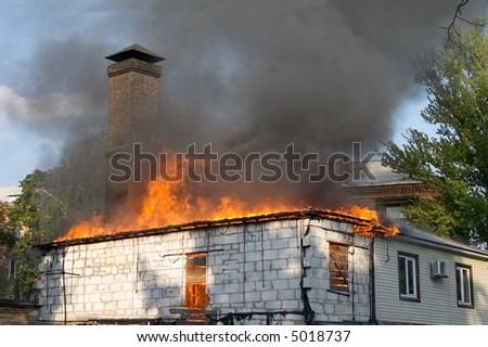 house on fire and clouds of black smoke - stock photo