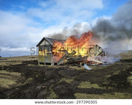 House on fire, burning down in paddock. - stock photo