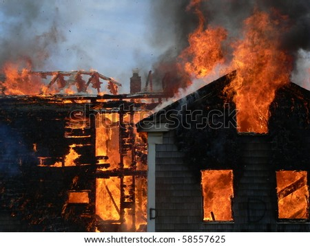 house on fires with flames shooting out - stock photo