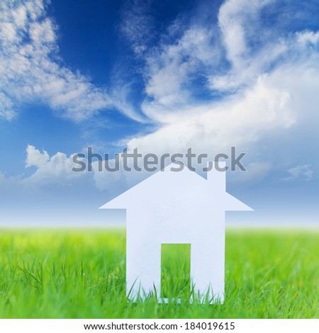 House on green field with blue sky