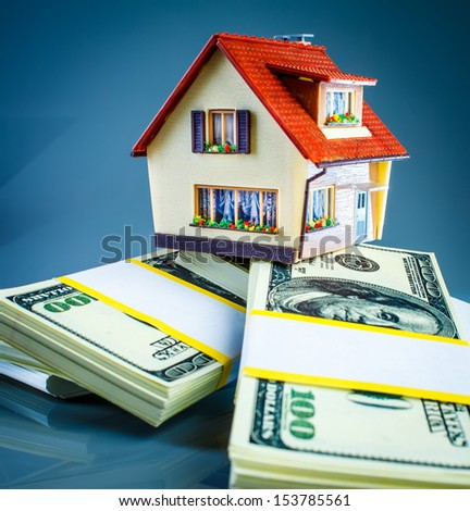 house on packs of banknotes on a blue background. - stock photo
