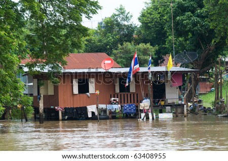 House on stilts during monsoon season in Thailand, with water overflowing the area around and under the house. - stock photo