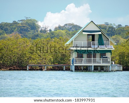 House on stilts over water with solar panels and dense tropical vegetation in background, Bocas del Toro, Caribbean sea, Panama - stock photo