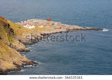 House on the mountain on a rocky coastline - stock photo