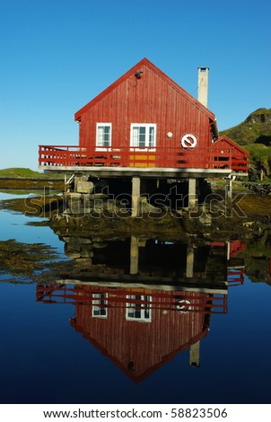 House on the sea coast and its reflection in still water - stock photo