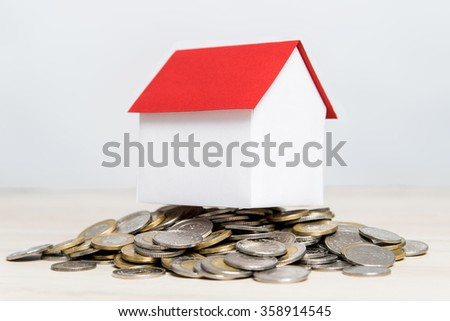 House on top laid with gold and silver coins - stock photo