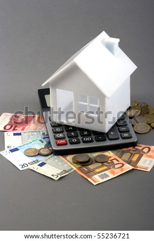 House on top of a calculator and money over gray background - stock photo