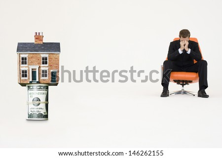 House on top of roll of bills with worried businessman on chair representing expensive real estate - stock photo