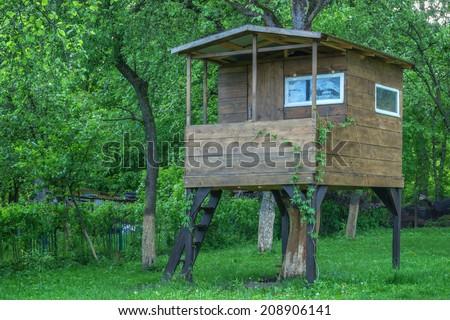 house on tree in summer garden - stock photo