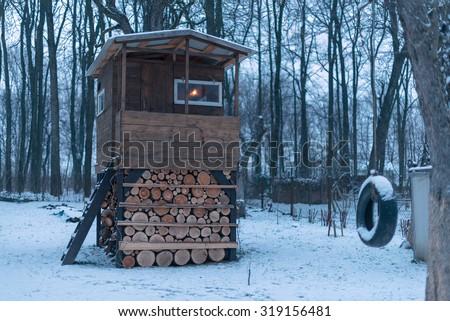 house on tree in winter garden - stock photo