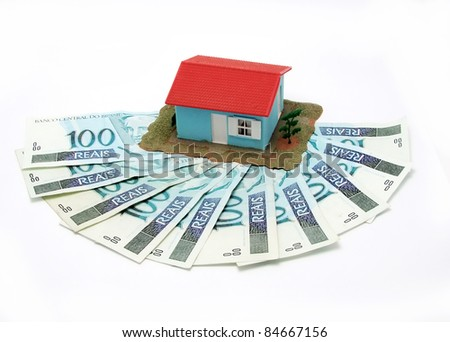 House over money against white background - mortgaging concept