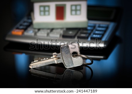 House over white with calculator and house keys. - stock photo