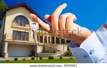 House owner/real estate agent giving away the keys - house out of focus - stock photo