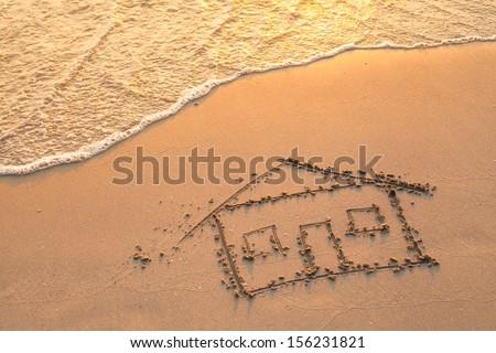 House painted on beach sand. - stock photo