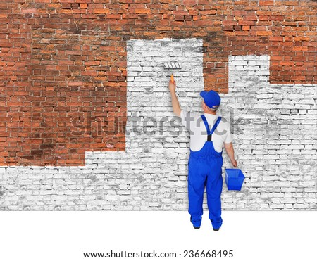 House painter covers old brick wall with white paint - stock photo
