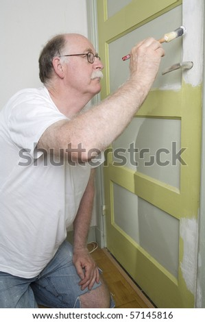 house painter is painting a door - stock photo