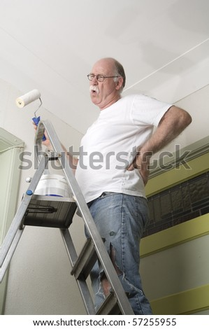 House painter is painting the roof and is having a backache - stock photo