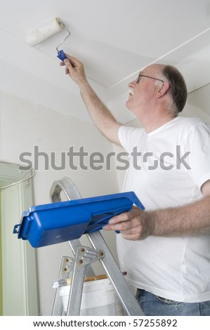 House painter is painting the roof with a roller - stock photo