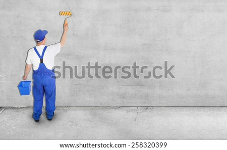 house painter paints blank gray wall, view from behind - stock photo