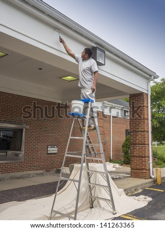 House painter rolling new paint on bank drive thru - stock photo