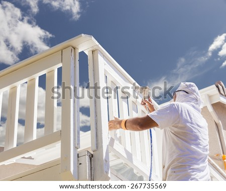 House Painter Wearing Facial Protection Spray Painting A Deck of A Home. - stock photo