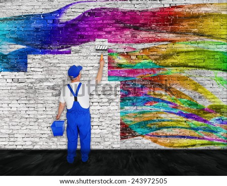 house painter with bucket fights with graffiti - stock photo