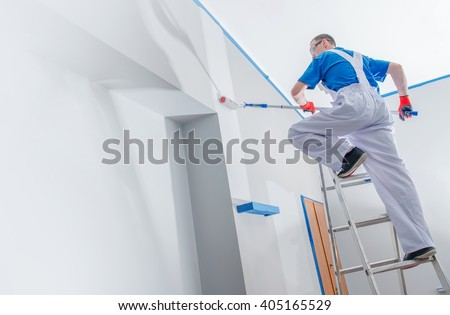 House Painting and Renovation Business Concept. Caucasian Male Painting House Room From the Ladder. - stock photo