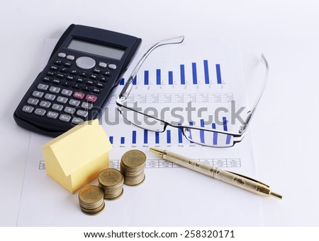 House paper and coins stack with Eyeglass and Calculator and pen on Chart for Loans money concept - stock photo