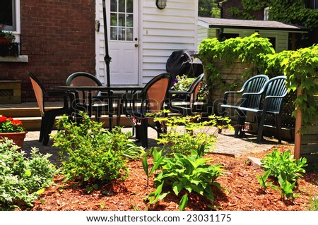 House patio with outdoor furniture and garden - stock photo