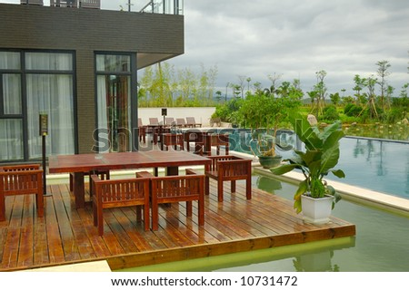 House patio with wooden table and swimming pool - stock photo