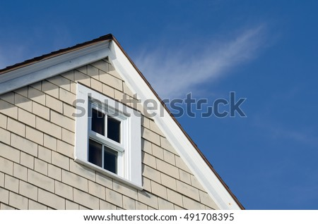 House peak with tan wooden siding and a white wood frame window against a beautiful blue sky.