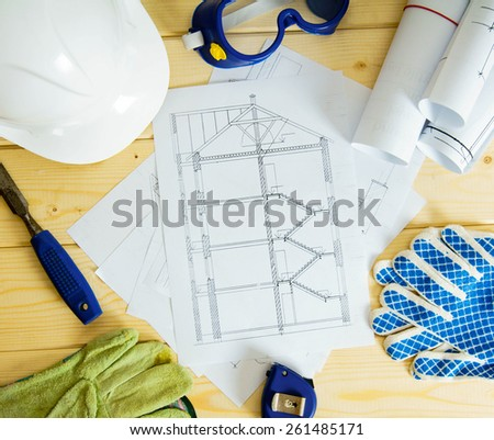 House planning. Repair work. Drawings for building, helmet, gloves and others tools on wooden background.