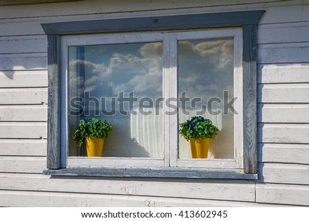 House plants on the windowsill of beautiful white wooden house.
