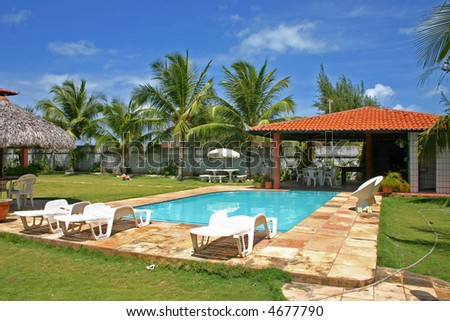 house pool with palmtrees and bright blue sky