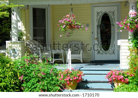 House porch with wicker furniture and flowers - stock photo
